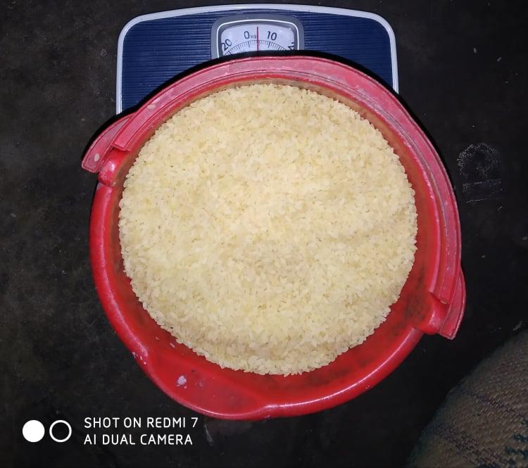 Volunteer A J Salim: Measuring rice carefully.
